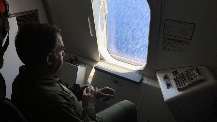 Un militaire argentin regarde à travers le hublot d'un avion américain au dessus de l'océan Atlantique, à la recherche du sous-marin, le 26 novembre 2017. (CARLOS REYES / AFP)
