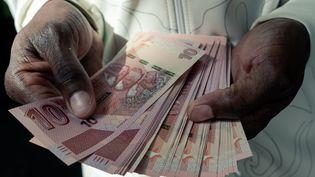 Un homme compte une liasse de nouveaux billets zimbabwéensà Harare, le 20 mai 2020. (JEKESAI NJIKIZANA / AFP)