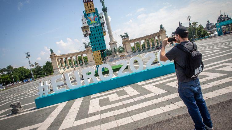 Un fan de football prend une photo des installations de l'Euro sur la place des Héros à Budapest, l'un des sites du championnat d'Europe de football, le 10 juin 2021. (FERENC ISZA / AFP)