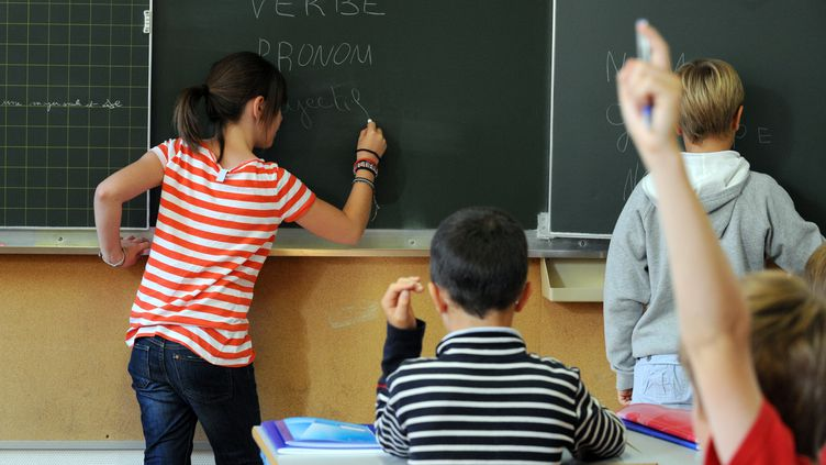 Une fillette écrit sur le tableau noir d'une classe d'école àNantes, le 5 décembre 2011. (FRANK PERRY / AFP)