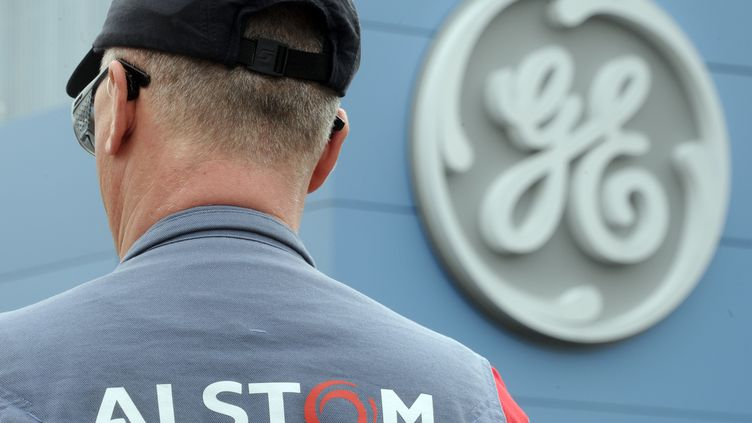 Un salarié d'Alstom devant le logo de l'usine General Electric de Belfort, le 29 avril 2014. (SEBASTIEN BOZON / AFP)