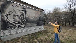 Un touriste prend une photo d'une mosaïque représentantYouri Gagarine,premier homme placé en orbite autour de la Terre. (NATALIA KOLESNIKOVA / AFP)