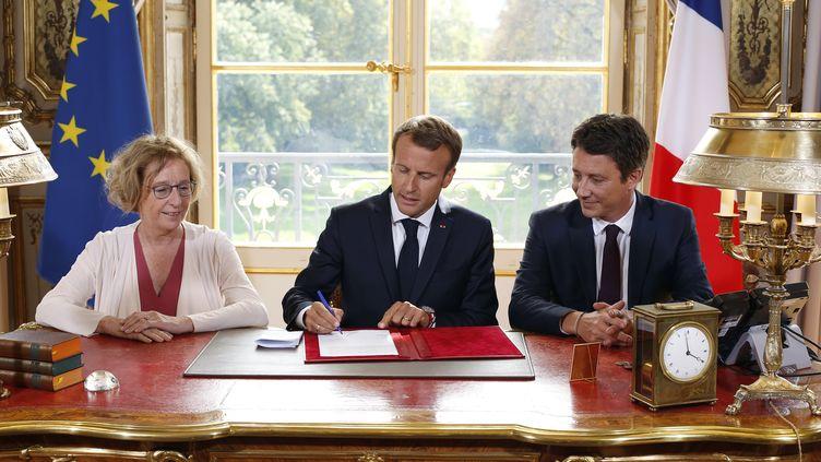 Emmanuel Macron signe la loi avenir professionnel, entouré par Muriel Pénicaud et Benjamin Griveaux à l'Elysée, le 5 septembre 2018. (THIBAULT CAMUS / AFP)