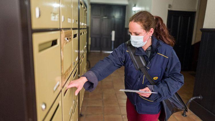 Une factrice distribue du courrier à Toulouse (Haute-Garonne), le 30 avril2020. (FR?D?RIC SCHEIBER / HANS LUCAS)
