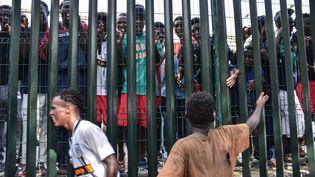 Deux hommes parlent à d'autres migrants, qui n'ont pu rentrer dans le territoire espagnol de Ceuta, dans le détroit de Gibraltar, le 22 août 2018. (JOAQUIN SANCHEZ / AFP)