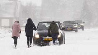 Des gens poussent leurs voitures dans la neige, le 7 février 2021, à Haarlem (Pays-Bas). (VINCENT JANNINK / ANP)