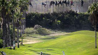 Des personnes jouent au golf tandis que derrière eux, des migrants qui tentés de traverser la frontière entre le Maroc et l'Espagne sont arrêtés par la police, Melilla (Espagne), le 22 octobre 2013. (REUTERS)