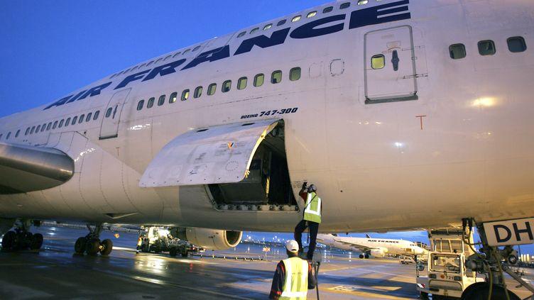 Des employésvérifient un avion d'Air France (illustration). (JACK GUEZ / AFP)