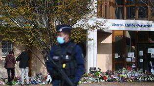 Des fleurs sont déposées aucollège du Bois d'Aulne, àConflans-Sainte-Honorine (Yvelines), le 19 octobre 2020, trois jours après l'assassinat de Samuel Paty. (ANNE-CHRISTINE POUJOULAT / AFP)