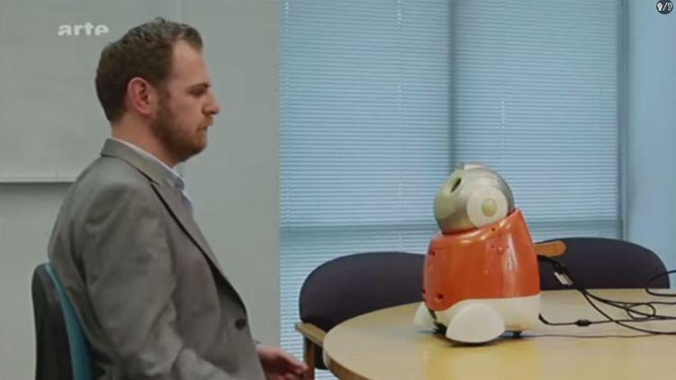 """Capture d'écran du documentaire """"Un monde sans humains"""", diffusé sur Arte le 23 octobre 2012. Ici, un homme passe un entretien face à un robot qui enregistre et filme les expressions de son visage. (YOUTUBE / FRANCETV INFO)"""
