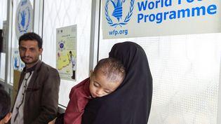 Une femme porte un enfant souffrant de malnutrition au centre de traitement du Programme alimentaire mondial, à Sanaa (Yémen), le 22 juin 2019. (MOHAMMED HUWAIS / AFP)