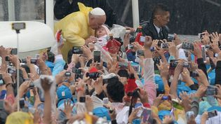 Le pape François embrasse un nouveau-né lors de son arrivée au parc Rizal de Manille (Philippines), dimanche 18 janvier 2015. (TED ALJIBE / AFP)