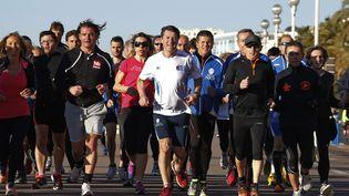 Le maire UMPsortant de Nice (Alpes-Maritimes), candidat à sa propre succession, Christian Estrosi (au centre), fait son jogging avec ses partisans, le 8 mars 2014. ( ERIC GAILLARD / REUTERS)