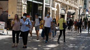 Des passants sur les Champs-Elysées, à Paris, le 5 août 2020. (PATRICIA MORIBE / HANS LUCAS / AFP)