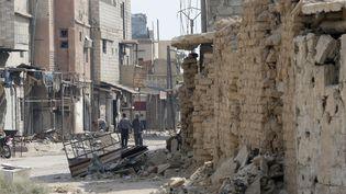 Un Syrien marche au milieu d'immeubles très endommagés dans une rue de Zabdin, dans la région de la Ghouta orientale, à la périphérie de Damas, le 8 octobre 2018. (LOUAI BESHARA / AFP)