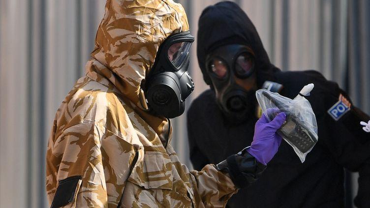 Un enquêteur en combinaison de protection,à Amesbury (Royaume-Uni), le 6 juillet 2018, pendant l'enquête sur l'empoisonnement au Novitchok de plusieurs Britanniques. (CHRIS J RATCLIFFE / AFP)