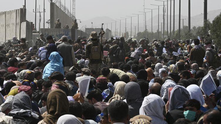 Des Afghans se rassemblent au bord d'une route près de l'aéroport de Kaboul, le 20 août 2021, dans l'espoir de fuir le pays après la prise de contrôle militaire de l'Afghanistan par les Talibans. (WAKIL KOHSAR / AFP)