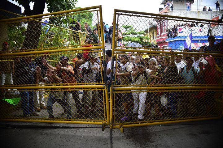 Desmigrants honduriens forcent uneclôture métallique du poste frontière guatémaltèque. (PEDRO PARDO / AFP)