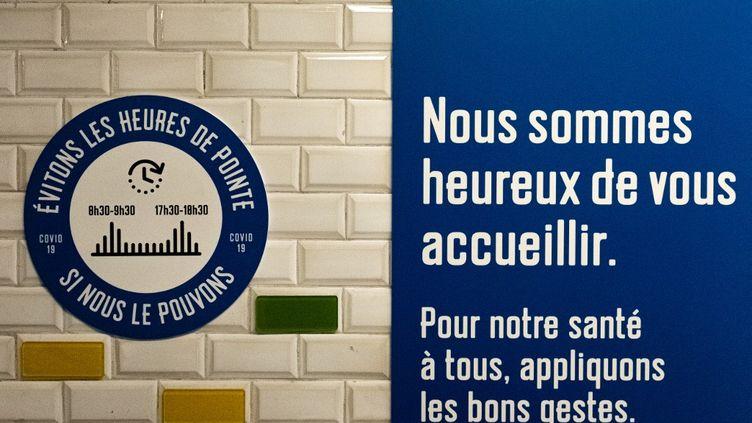 Une affiche appelant à éviter les heures de pointe en raison de l'épidémie de coronavirus est installée dans le métro, à Paris, le 7 mai 2020. (SAMUEL BOIVIN / NURPHOTO / AFP)