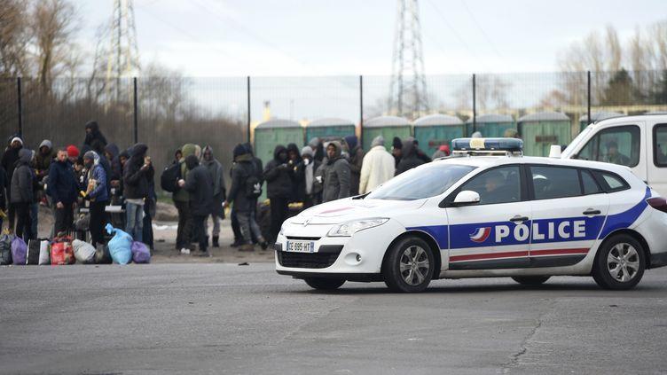 Un véhicule de police à proximité d'un groupe de migrants à Calais, le 2 février 2018. (PHILIPPE HUGUEN / AFP)