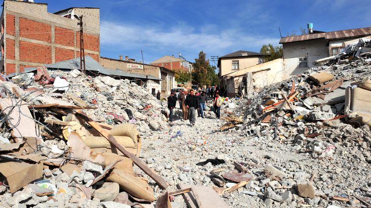 Les habitants d'Ercis au milieu de leur ville en ruines, le 24 octobre,au lendemain du séisme qui a frappé la province de Van, dans l'est de la Turquie. (MUSTAFA OZER/AFP)