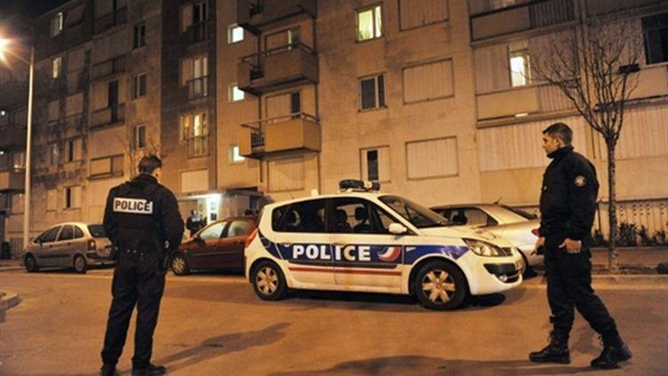 Des policiers montent la garde devant l'immeuble où deux personnes ont péri poignardées, à Nanterre (9/2/2011) (AFP / Etienne Laurent)