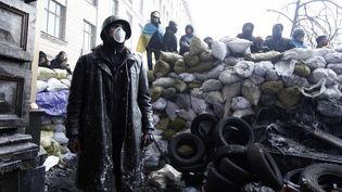 Des manifestants anti-gouvernement derrière des barricades place de l'Indépendance à Kiev (Ukraine), le 25 janvier 2014. (VASILY FEDOSENKO / REUTERS)
