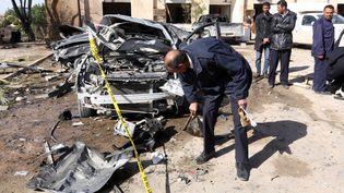 Des hommes des services de sécurité inspectent le site d'un attentat suicide à la voiture piégée à Zliten (Libye) le 7 janvier 2016. (MAHMUD TURKIA / AFP)