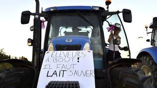 Une femme sur un tracteur, devant la siège de Lactalis, à Laval (Mayenne), le 22 août 2016. (JEAN-FRANCOIS MONIER / AFP)