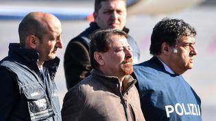 L'ex-activiste italien Cesare Battisti est escorté par des policiers sur le tarmac de Rome-Ciampino (Italie), le 14 janvier 2019. (ALBERTO PIZZOLI / AFP)