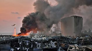 Un hélicoptère tente d'éteindre les flammes après l'explosion, le 4 août 2020 à Beyrouth (Liban). (AFP)