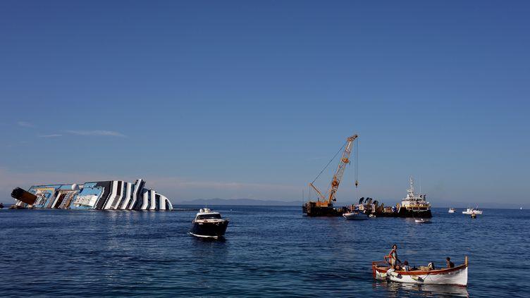 """L'épave du """"Costa Concordia"""", toujours en cours de démantèlement près des côtes de l'île du Giglio (Italie), le 23 juin 2012. (VINCENZO PINTO / AFP)"""
