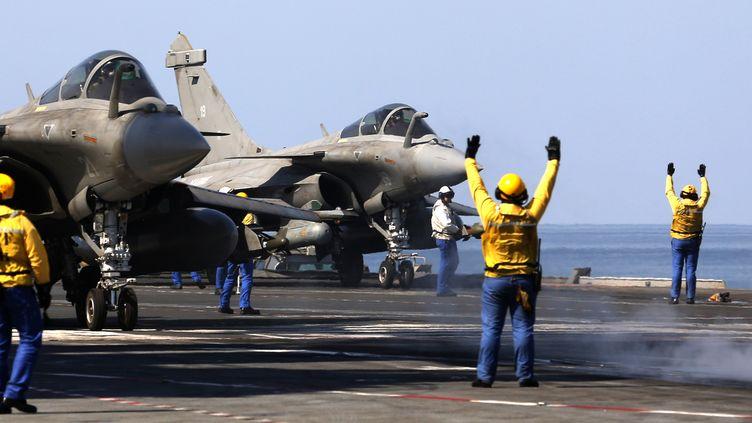 """Des Rafale se préparent à décoller du porte-avions français """"Charles-de-Gaulle"""", mercredi 25 février 2015, dans le golfe Persique. (PATRICK BAZ / AFP)"""