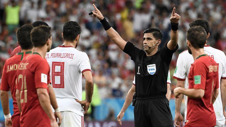 L'arbitre paraguayenEnrique Caceres demande l'assistance vidéo lors du match de Coupe du monde entre l'Iran et le Portugal, le 25 juin 2018 àSaransk(Russie). (FILIPPO MONTEFORTE / AFP)