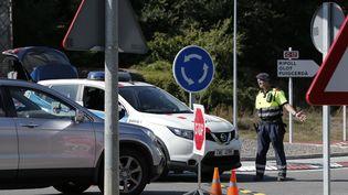 Un policier contrôle des véhicules à Ripoll (Catalogne), dimanche 20 août 2017. (PAU BARRENA / AFP)