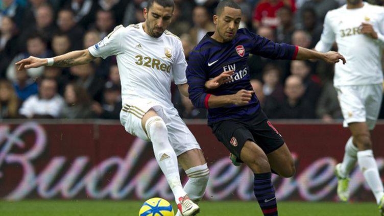 A l'image de ce duel entre Théo Walcott et Chico Flores, Arsenal et Swansea n'ont pas réussi à se départager.  (ADRIAN DENNIS / AFP)