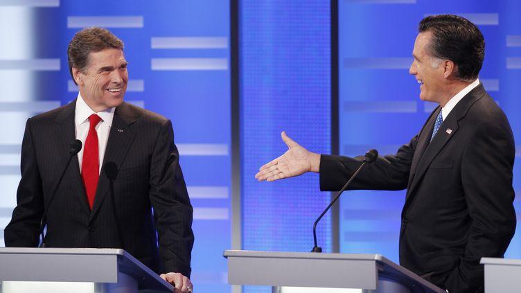 Le candidat à l'investiture républicaine Mitt Romney (à droite) s'adresse à son rival Rick Perry (à gauche) lors du débat de Des Moines dans l'Iowa (Etats-Unis), le 10 décembre 2011. (JEFF HAYNES / REUTERS)
