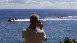 Un touriste prend des Canadairs en photo, près de Sisco, en Haute-Corse, le 12 août 2017. (PASCAL POCHARD-CASABIANCA / AFP)