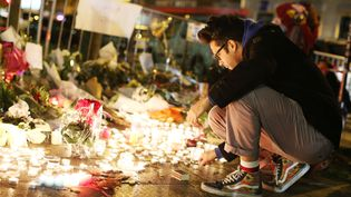 Un hommeallumant une bougie devant le Bataclan, le 14 novembre 2015, au lendemain de l'attaque terroriste. (MALTE CHRISTIANS / DPA / AFP)
