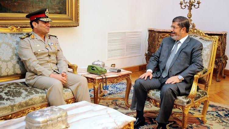 Le ministre de la Défense (G),Abdel Fattah Al-Sissi, et leprésident égyptien Mohamed Morsi, le 13 août 2012, au Caire (Egypte). (EGYPTIAN PRESIDENCY / AFP)
