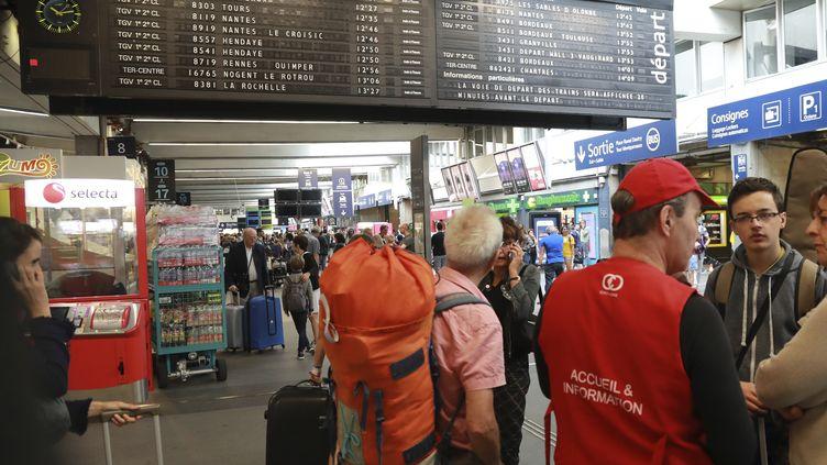 Un employé de la SNCF renseigne des voyageurs en gare de Montparnasse, à Paris, le 30 juillet 2017. (JACQUES DEMARTHON / AFP)