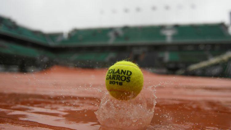 Une balle de tennis rebondit dans la pluie parisienne, à Roland-Garros (Paris), le 31 mai 2016. (MARTIN BUREAU / AFP)