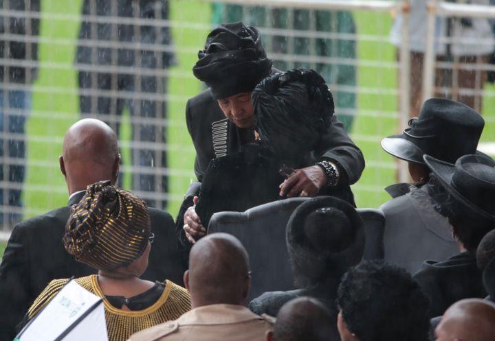 Winnie Madikizela-Mandela et Graça Machel, deux ex-épouses de Nelson Mandela, s'embrassent, le 10 décembre 2013, lors de l'hommage rendu au prix Nobel de la paix, àJohannesburg (Afrique du Sud). (CHRISTOPHER FURLONG / GETTY IMAGES EUROPE / AFP)