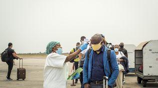 Une employée de l'équipe d'intervention prend la température des passagers arrivant à l'aéroport international de Kinshasa, le 15 août 2020, dans le cadre des mesures sanitaires prises pour lutter contre le coronavirus. (ARSENE MPIANA / AFP)