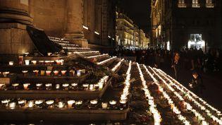 Les passantsse sont réunis en silence autour d'autels spontanésinstallés un peu partout dans le vieux Lyon, comme ici sur les marches de l'hôtel de ville. (LAURENT CIPRIANI / AP / SIPA)