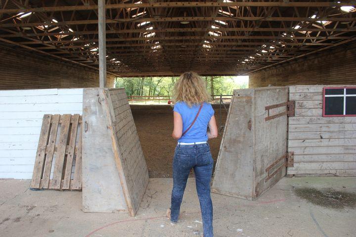 Marlène entre dans le manège d'équitation du hameau, qui ne sera plus destiné à accueillir des chevaux, mais qui pourrait devenir une salle des fêtes. (CLEMENT PARROT / FRANCETV INFO)