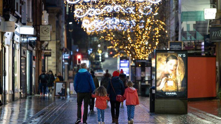 Une famille fait son shopping de Noël à Manchester, le 21décembre 2020, alors qu'un nouveau variant du coronavirus prolifère au Royaume-Uni depuis le mois de décembre. (MI NEWS / NURPHOTO / AFP)