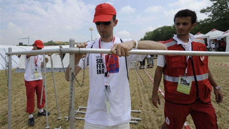 de jeunes volontaires de la Croix-Rouge préparent une réserve d'eau, à Solferino (Italie), le 26/06/09 (© AFP/Damien Meyer)