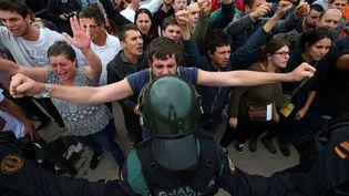 Des partisans du référendum d'indépendance en Catalogne face à la police espagnole, le 1er octobre 2017 à Barcelone. (ALBERT GEA / REUTERS)