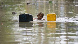 Un homme nage dans une rue inondée à Kalay, dans la région de Sagaing(centre de la Birmanie), le 3 août 2015. (YE AUNG THU / AFP)
